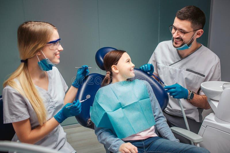 Het positieve gelukkige meisje zit als tandvoorzitter en kijkt en de mannelijke glimlach van tandartsHe aan haar Vrouwelijke ook  royalty-vrije stock afbeeldingen