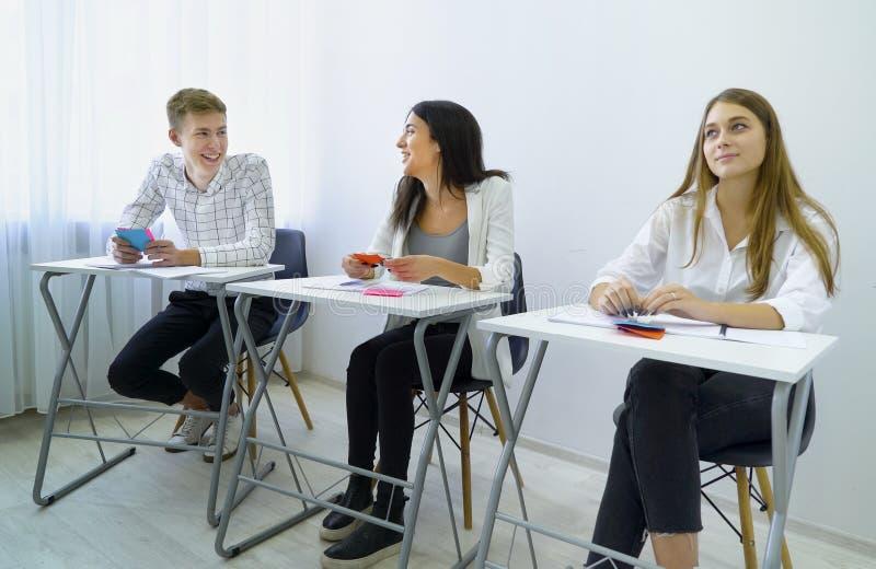 Het positieve het glimlachen mannelijke en vrouwelijke groepswerk van de studentenpraktijk en voert communicatie vaardigheden uit royalty-vrije stock afbeeldingen