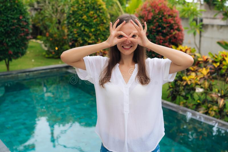 Het positieve grappige donkerbruine meisje toont o.k. teken, aantoont dat alles boete stock foto's