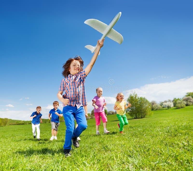 Het positieve het lopen jonge geitjes en jongensstuk speelgoed van het holdingsvliegtuig royalty-vrije stock fotografie