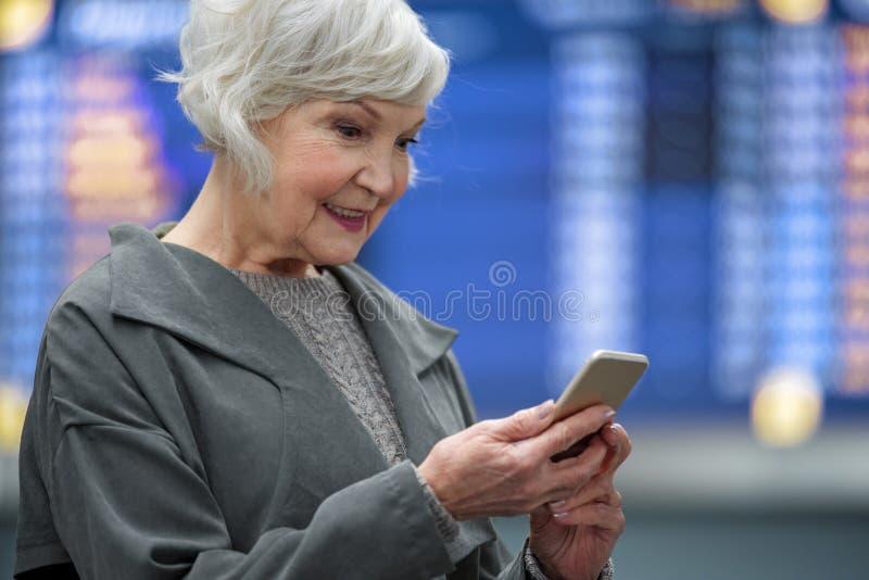 Het positieve hogere wijfje houdt mobiele telefoon met glimlach royalty-vrije stock foto
