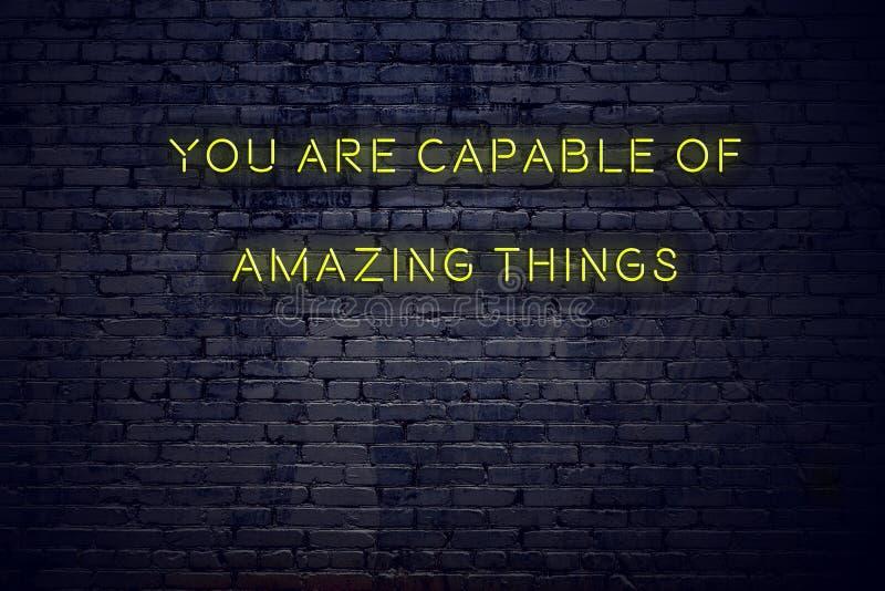 Het positieve inspirerende citaat op neonteken tegen bakstenen muur u is geschikt voor verbazende dingen vector illustratie