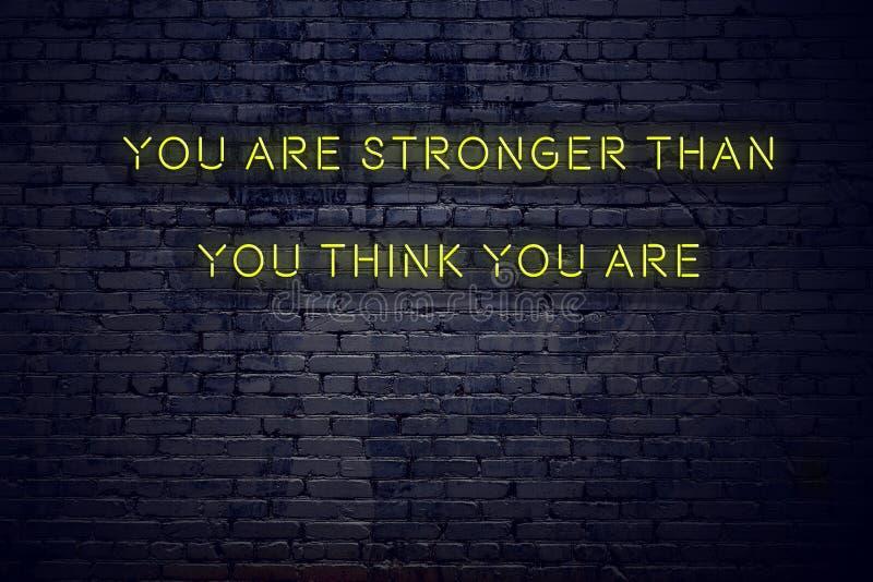 Het positieve inspirerende citaat op neonteken tegen bakstenen muur u is sterker dan u denkt u bent vector illustratie