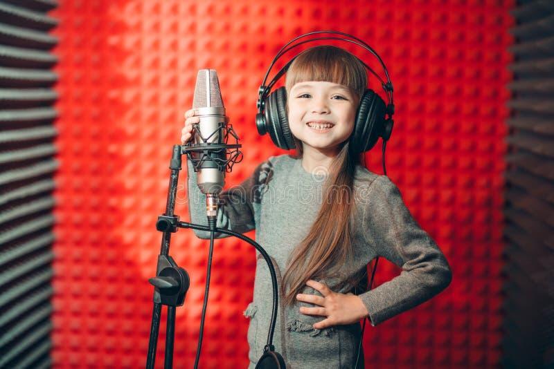 Het positieve jong geitje stellen aan canera tijdens zingende klassen stock fotografie