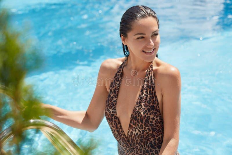 Het positieve magnetische jonge model stellen in zwembad, die complex bij kuuroordhotel zijn, hebbend prettige gelaatsuitdrukking stock foto's