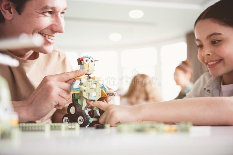 Het positieve mannetje en meisjes spelen met robot royalty-vrije stock fotografie