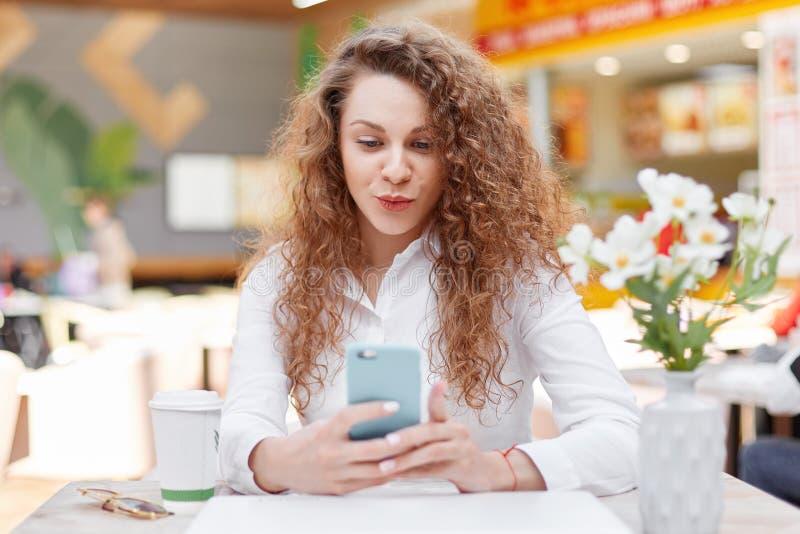 Het positieve mooie wijfje met krullend dichtbegroeid haar houdt celtelefoon surfes Internet op moderne celtelefoon of maakt self stock fotografie