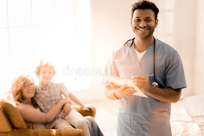Het positieve opgetogen pediater stellen op camera stock foto