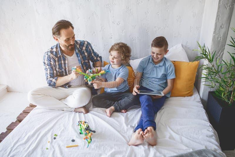 Het positieve papa spelen met zonen royalty-vrije stock fotografie