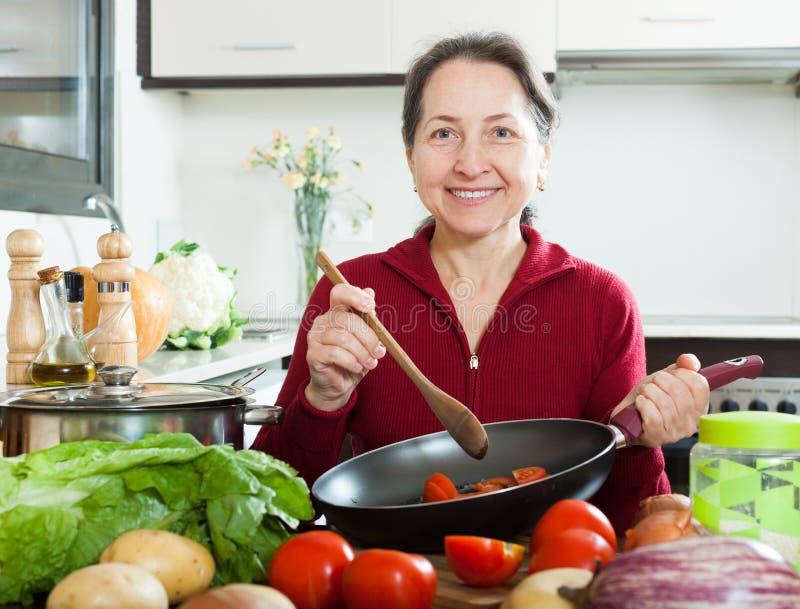 Het positieve rijpe vrouw koken met koekepan stock fotografie
