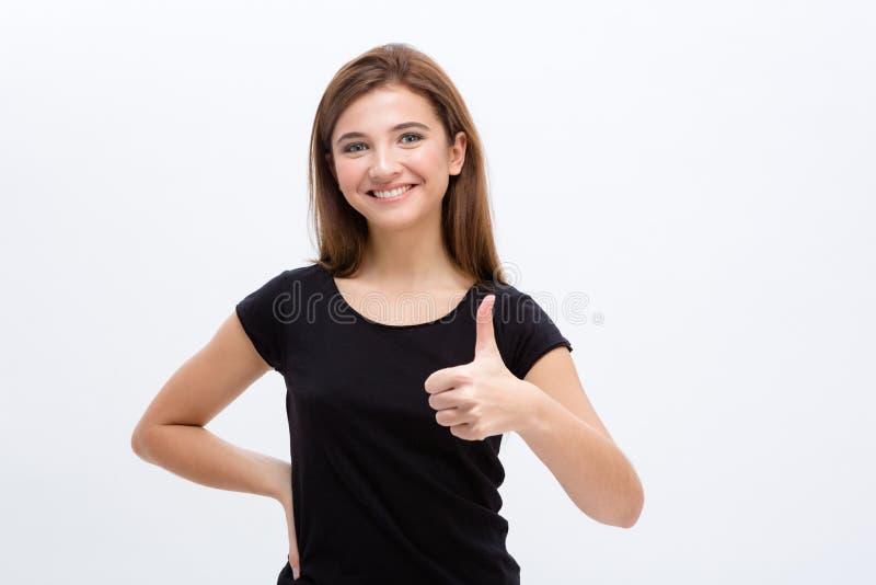 Het positieve vrij vrolijke jonge vrouw tonen beduimelt omhoog royalty-vrije stock fotografie