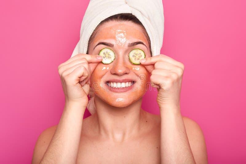 Het positieve vrouwelijke model vertroetelt huid, toepast schoonheidsmasker op gezicht, heeft cucmber op ogen, ruim glimlacht, to stock afbeelding