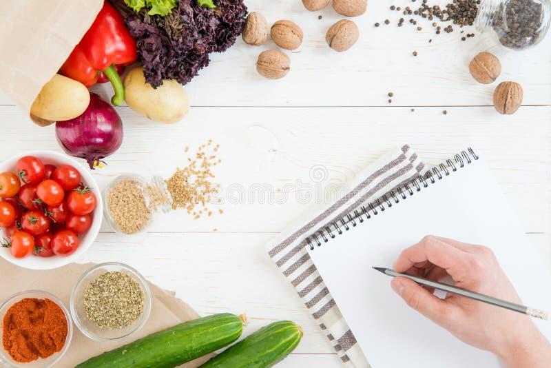 Het potlood van de persoonsholding en het schrijven recept in kookboek terwijl het koken royalty-vrije stock fotografie