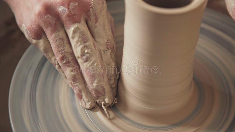 Het pottenbakkers` s werk die een spinnend pottenbakkers` s wiel gebruiken Slechts handen royalty-vrije stock fotografie