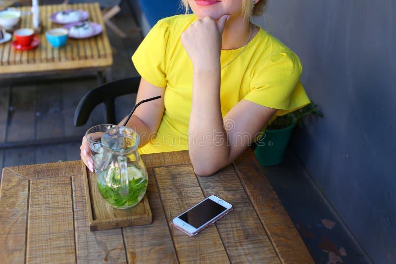 Het prachtige jonge meisje glimlachen, houdt glas in hand, giet lemonad stock foto's