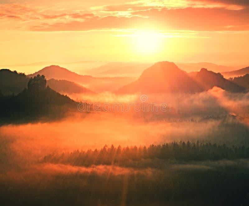 Het prachtige rode wekken De herfst mooie vallei De pieken van heuvels plakken uit van stralen van de mist de rode en oranje Zon royalty-vrije stock afbeeldingen