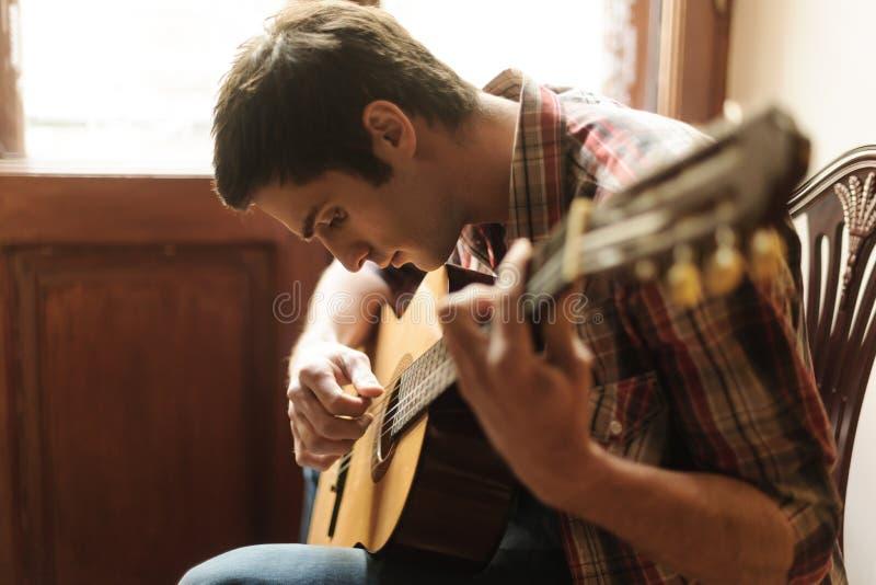 Het praktizeren in het spelen gitaar stock afbeeldingen