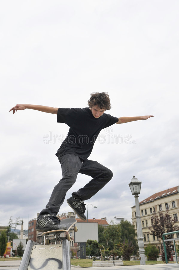 Het praktizeren van de jongen het met een skateboard rijden stock foto's