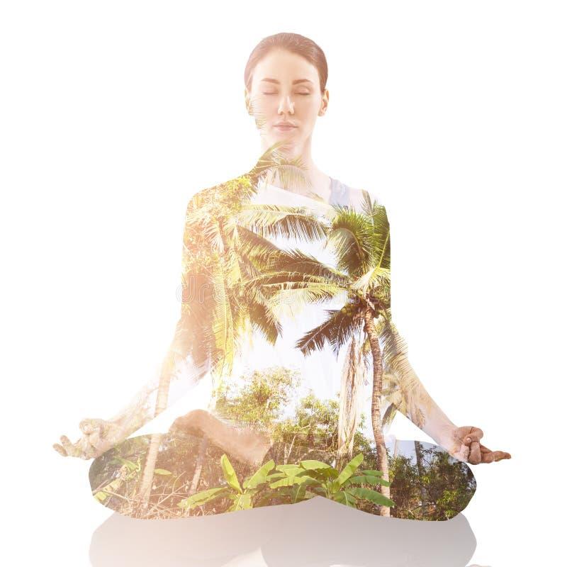 Het praktizeren van de vrouw yoga in de lotusbloempositie royalty-vrije stock afbeelding