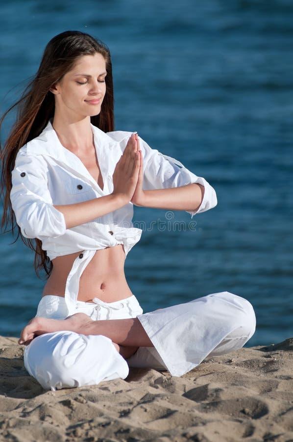 Het praktizeren van de vrouw yoga op het strand stock fotografie