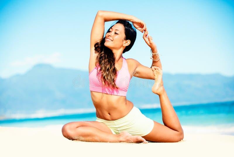 Het praktizeren van de vrouw yoga op het strand stock afbeeldingen