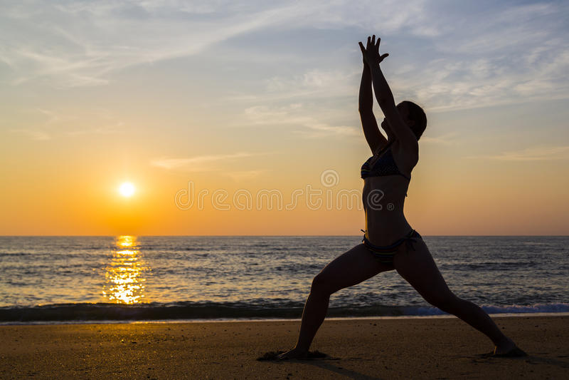 Het praktizeren van de vrouw yoga op het strand royalty-vrije stock fotografie