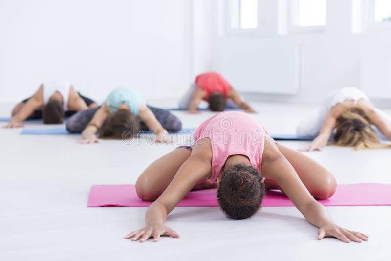 Het praktizeren yoga bij de gymnastiek stock afbeeldingen