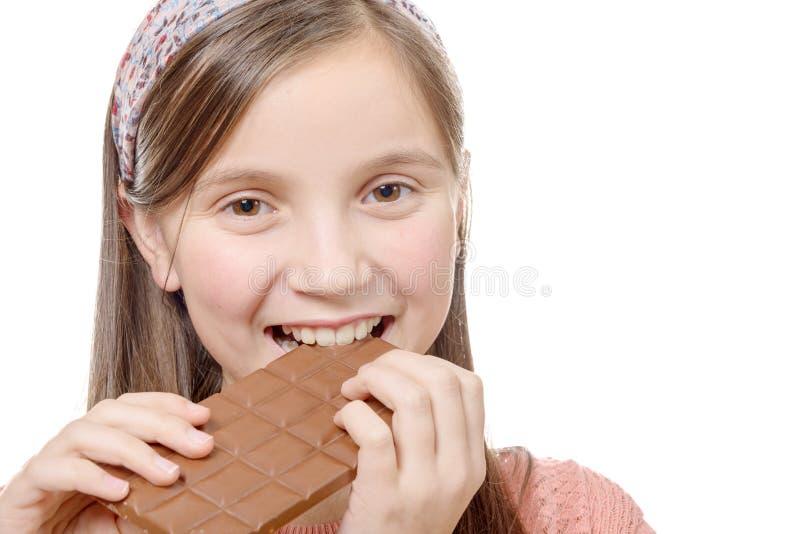 Het Preteenmeisje eet chocolade, op wit wordt geïsoleerd dat stock afbeelding