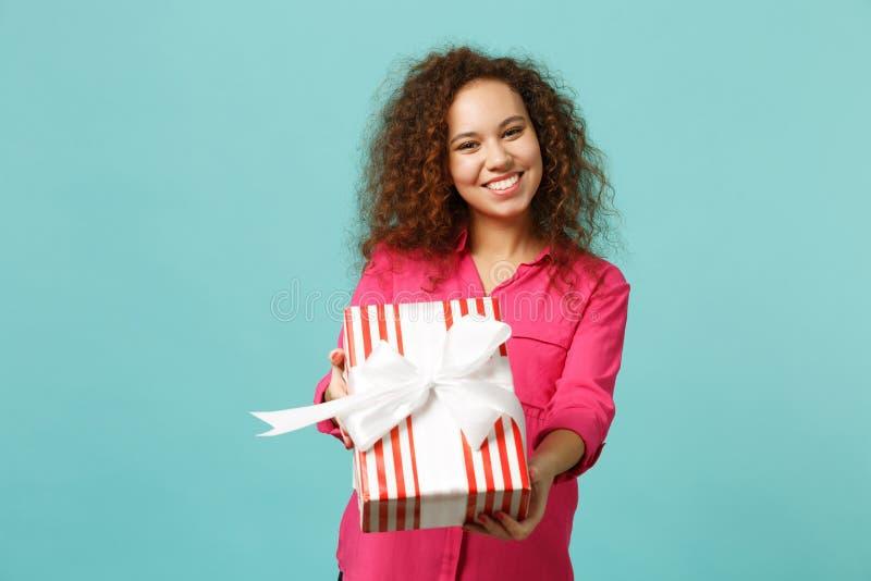 Het prettige Afrikaanse meisje in roze kleren houdt rode gestreepte huidige die doos met giftlint op blauwe turkooise muur wordt  royalty-vrije stock afbeelding