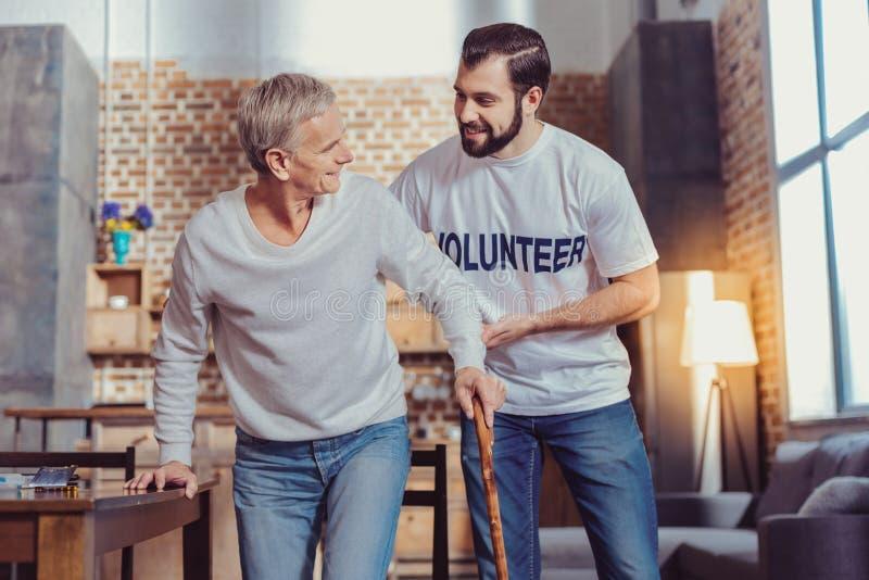 Het prettige betrouwbare vrijwilligers teruggetrokken steunen en het glimlachen royalty-vrije stock afbeelding