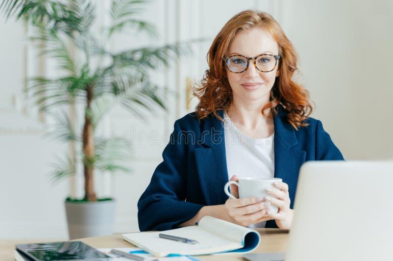 Het prettige kijken de elegante vrouwelijke punten van freelancerboeken op Webopslag, leest nieuws in Internet, schrijft nota's i stock afbeelding