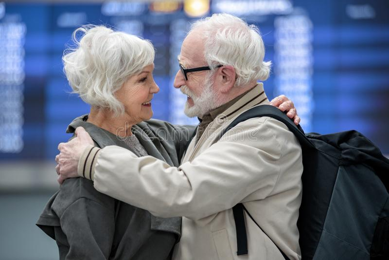 Het prettige oude paar omhelst in terminal stock afbeelding