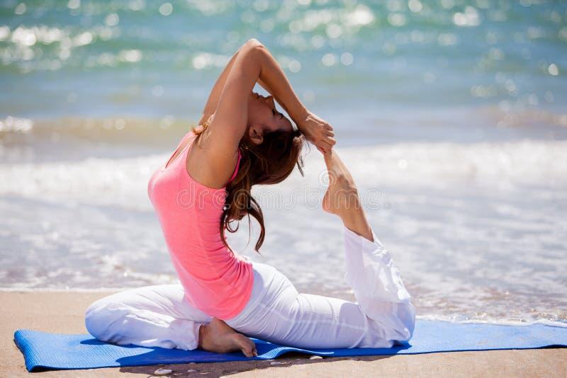 Het proberen van wat yoga stelt bij het strand stock foto's
