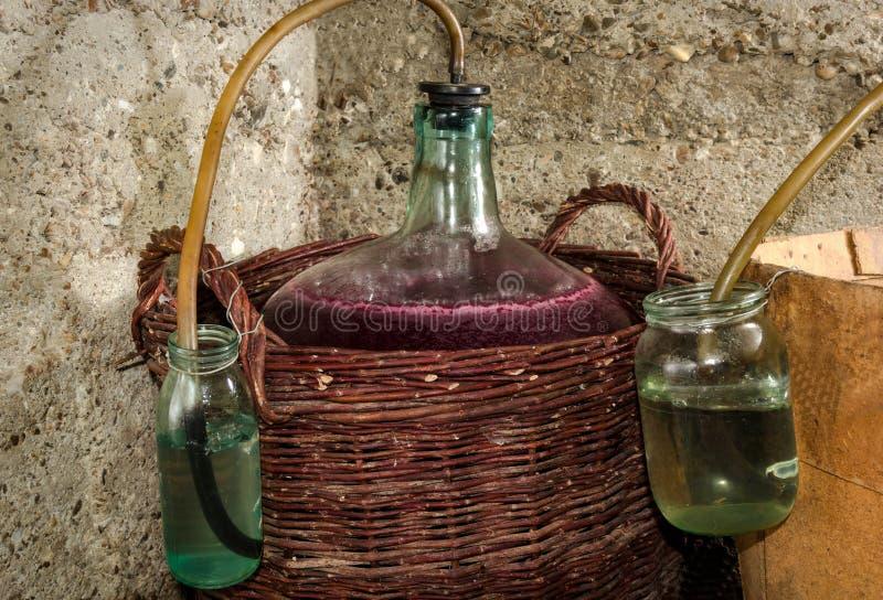 Het procédé van de wijngisting in wijnmandeflessen stock afbeeldingen