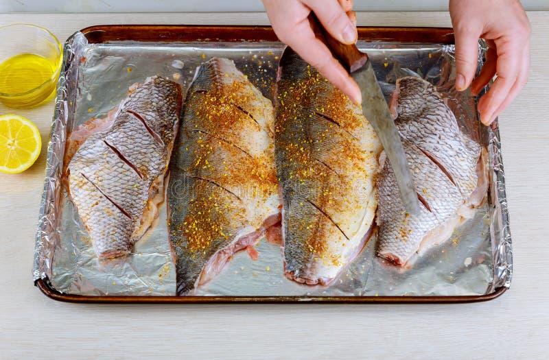 Het proces om Dorado-vissen met citroen en kruidenhanden te koken kookt omhoog besnoeiing de vissen stock foto's