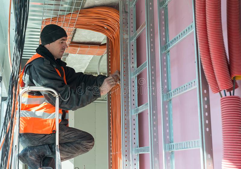 Het proces om een gele kabel voor Internet vast te maken stock afbeelding