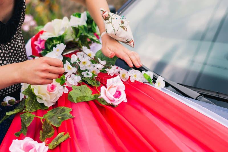 Het proces om een huwelijksauto met kunstbloemen en gordijn te verfraaien stock afbeelding