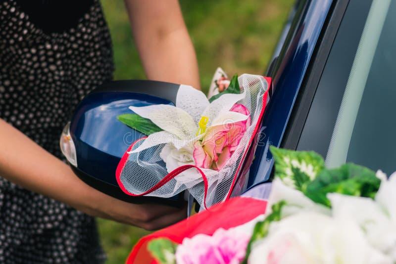 Het proces om een huwelijksauto met kunstbloemen en gordijn te verfraaien stock foto's