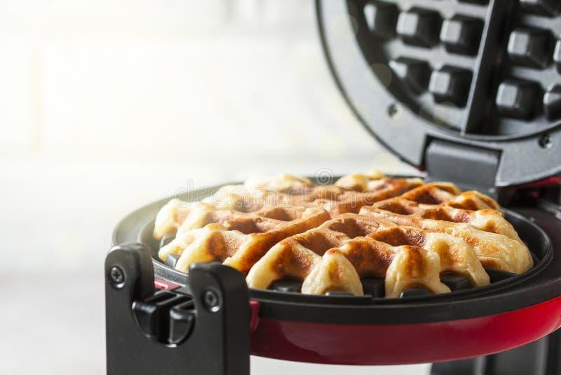 Het proces om eigengemaakte wafels te maken Vers gebakken wafels in een wafelijzer royalty-vrije stock afbeeldingen