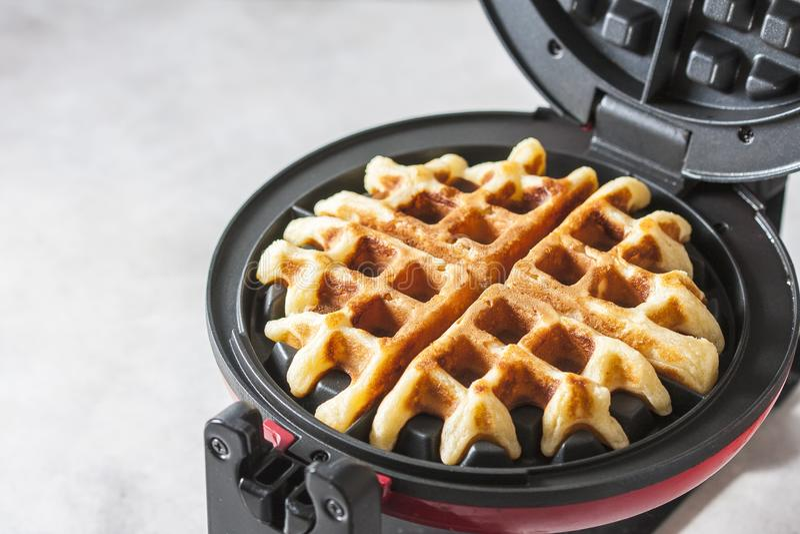 Het proces om eigengemaakte wafels te maken Vers gebakken wafels in een wafelijzer royalty-vrije stock foto