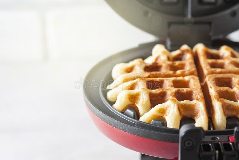 Het proces om eigengemaakte wafels te maken Vers gebakken wafels in een wafelijzer stock foto