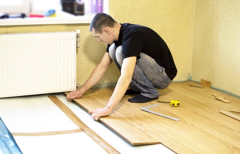 Het proces om gelamineerde houten op de vloer te installeren stock afbeelding