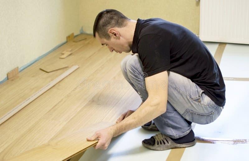 Het proces om gelamineerde houten op de vloer te installeren stock fotografie