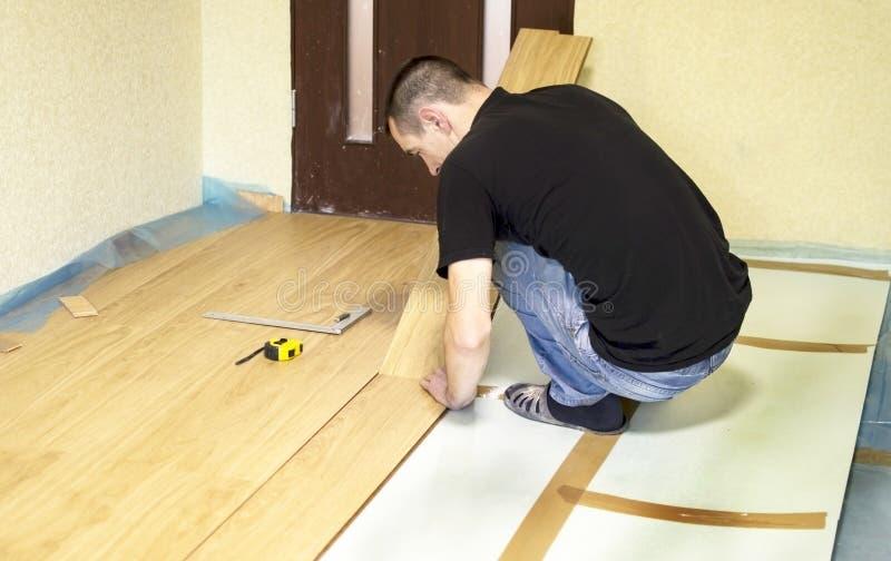 Het proces om gelamineerde houten op de vloer te installeren stock foto's