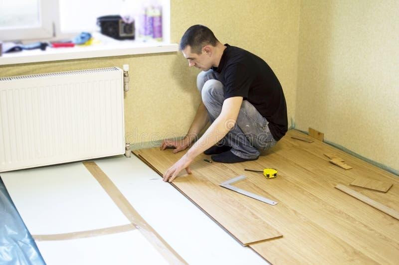 Het proces om gelamineerde houten op de vloer te installeren stock foto