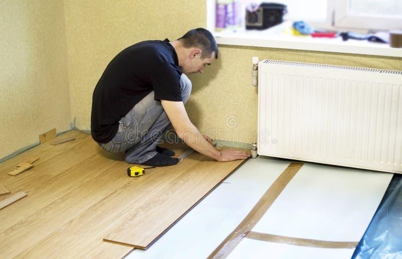 Het proces om gelamineerde houten op de vloer te installeren royalty-vrije stock afbeeldingen