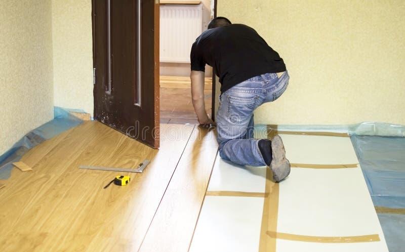 Het proces om gelamineerde houten op de vloer te installeren royalty-vrije stock foto's