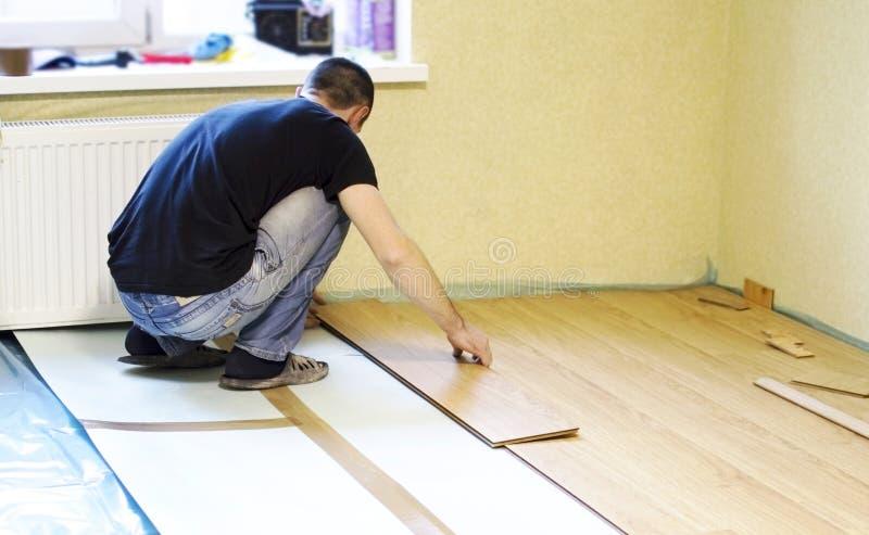 Het proces om gelamineerde houten op de vloer te installeren stock afbeeldingen