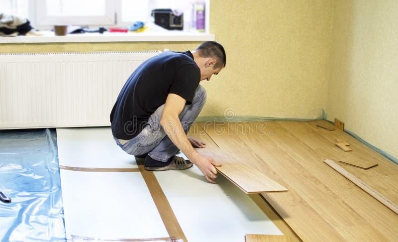 Het proces om gelamineerde houten op de vloer te installeren royalty-vrije stock afbeelding