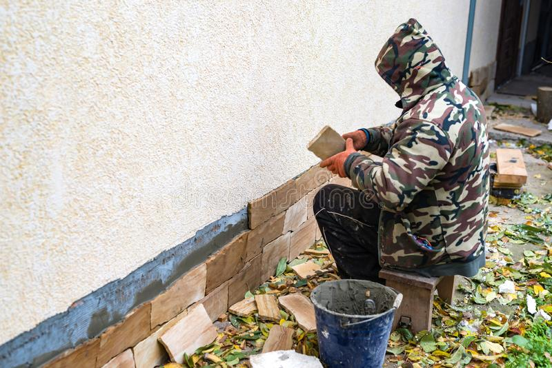 Het proces om zandsteen decoratieve tegels te installeren stock foto's